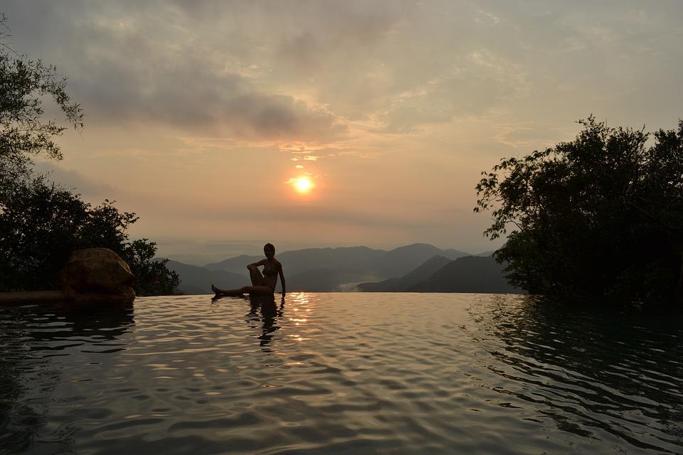 Девушка в бассейне на фоне заката