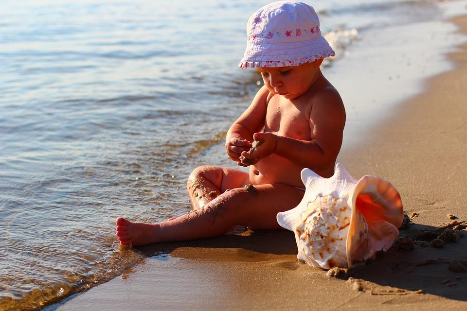 Ребенок с ракушкой на пляже