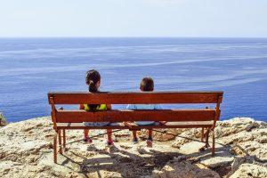 Дети на лавочке смотрят на море