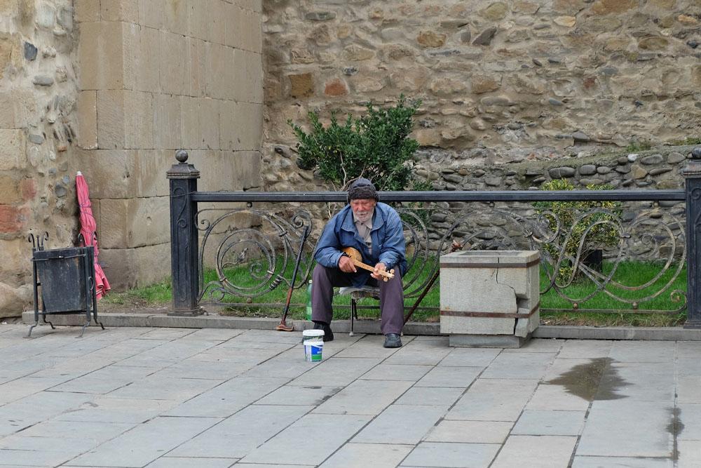 Старик играет на фандури под стенами Свитицховели