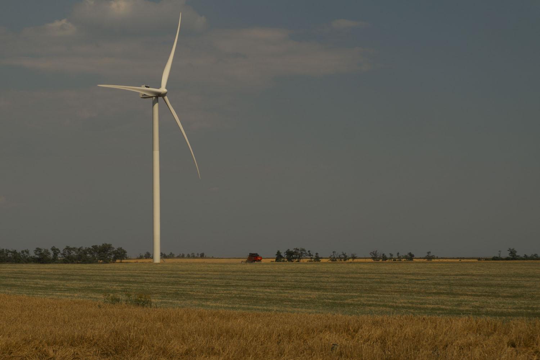 Комбайн собирает пшеницу под ветрогенераторами